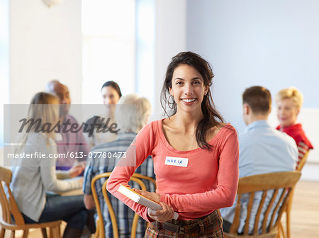 Portrait of young woman in front of seated group. Stock Photo - Premium Royalty-Free, Image code: 613-07780473