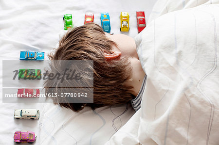 Boy sleeping with toy cars Stock Photo - Premium Royalty-Free, Image code: 613-07780942