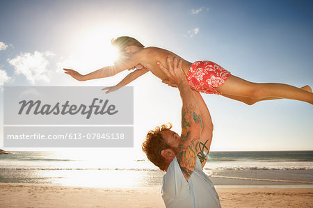 Father and son (6 - 8 years) playing on beach Stock Photo - Premium Royalty-Free, Image code: 613-07845138