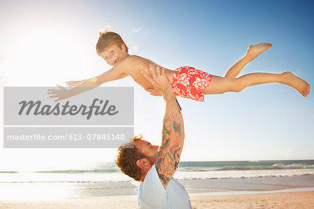 Father and son (6 - 8 years) playing on beach Stock Photo - Premium Royalty-Free, Image code: 613-07845140