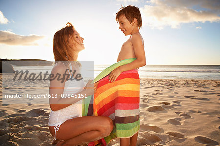 Mother on beach, wrapping son in towel Stock Photo - Premium Royalty-Free, Image code: 613-07845151