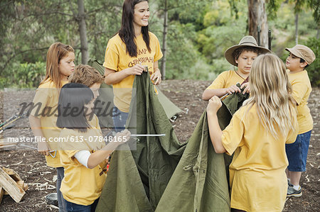 Camp counsellor and young campers setting up canvas tent Stock Photo - Premium Royalty-Free, Image code: 613-07848165