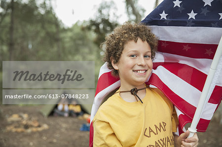 Portrait of young boy holding American flag in forest Stock Photo - Premium Royalty-Free, Image code: 613-07848223
