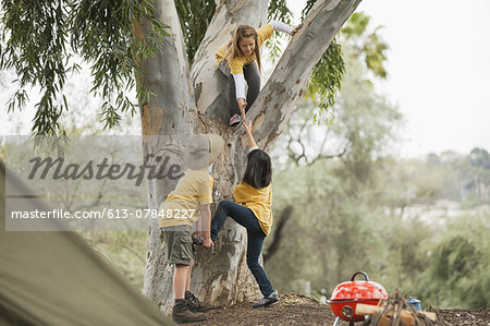 Young children helping friend to climb tree in forest Stock Photo - Premium Royalty-Free, Image code: 613-07848227