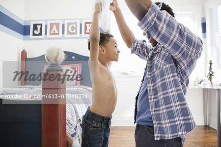 Father removing son's shirt in bedroom Stock Photo - Premium Royalty-Free, Image code: 613-07848374