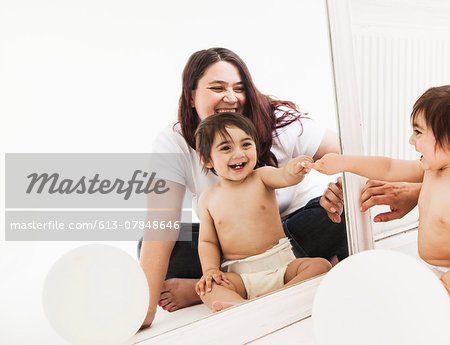 Mother and baby smiling at reflection in mirror Stock Photo - Premium Royalty-Free, Image code: 613-07848646