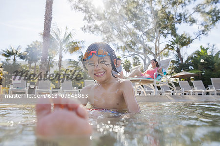 Smiling boy sitting in pool with parents in background Stock Photo - Premium Royalty-Free, Image code: 613-07848883