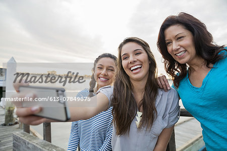 Smiling mother and daughters taking self portrait with smartphone Stock Photo - Premium Royalty-Free, Image code: 613-07849075