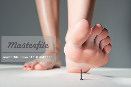 Foot about to step on nail Stock Photo - Premium Royalty-Free, Image code: 613-07849220