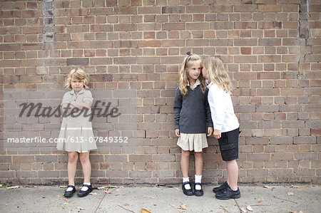 Bullying and whispering in school playground Stock Photo - Premium Royalty-Free, Image code: 613-07849352
