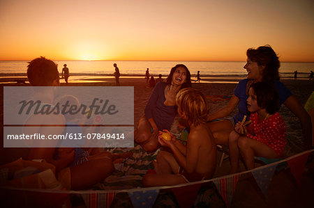 Family with grandmother relaxing on beach Stock Photo - Premium Royalty-Free, Image code: 613-07849414