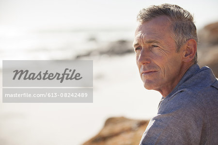 Close up of mature man relaxing on beach Stock Photo - Premium Royalty-Free, Image code: 613-08242489