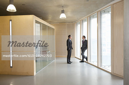 Businessmen talking in office hallway Stock Photo - Premium Royalty-Free, Image code: 613-08242703