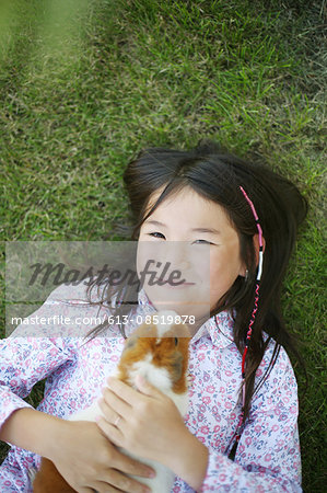 A girl hugging a hamster Stock Photo - Premium Royalty-Free, Image code: 613-08519878
