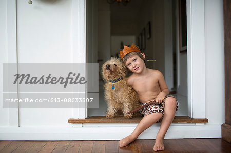 Young boy at home cuddling dog, sword, kings crown Stock Photo - Premium Royalty-Free, Image code: 613-08633507