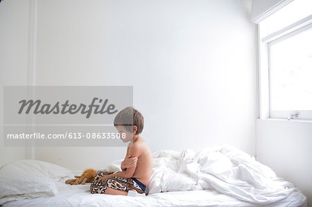 Young boy upset on white bed sheets in room Stock Photo - Premium Royalty-Free, Image code: 613-08633508