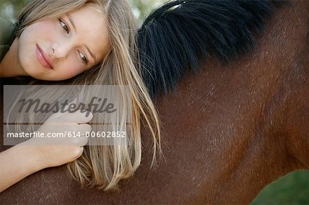 Young woman lying on her horse Stock Photo - Premium Royalty-Free, Image code: 614-00602852