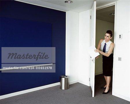 Woman opening door to office - Stock Photo