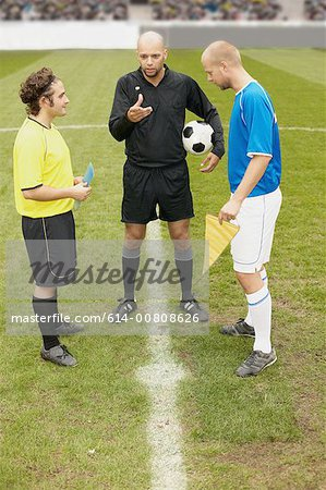 Referee tossing a coin Stock Photo - Premium Royalty-Free, Image code: 614-00808626