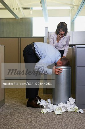 Businessman being sick in rubbish bin Stock Photo - Premium Royalty-Free, Image code: 614-00844051