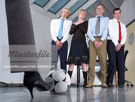 Kicking football at colleagues Stock Photo - Premium Royalty-Free, Image code: 614-00844334