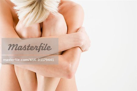 Nude woman hugging her legs Stock Photo - Premium Royalty-Free, Image code: 614-01179441