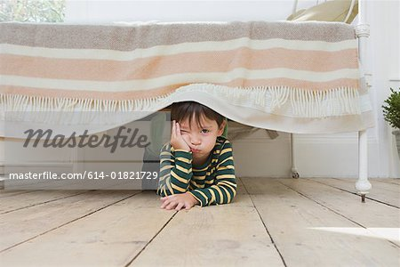 Boy hiding under a bed Stock Photo - Premium Royalty-Free, Image code: 614-01821729