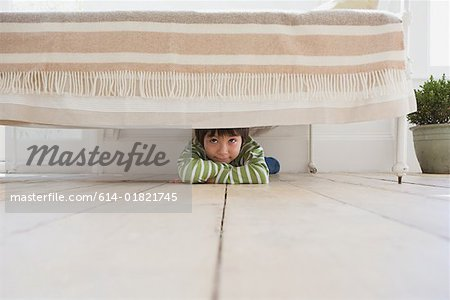 Boy hiding under a bed Stock Photo - Premium Royalty-Free, Image code: 614-01821745