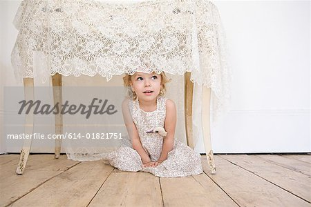 Girl hiding under a table Stock Photo - Premium Royalty-Free, Image code: 614-01821751