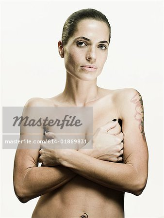 Woman covering her breasts Stock Photo - Premium Royalty-Free, Image code: 614-01869831