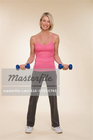 A woman lifting dumbbells Stock Photo - Premium Royalty-Free, Image code: 614-02050749