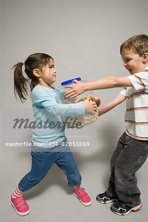 A boy and girl fighting over a jar of biscuits Stock Photo - Premium Royalty-Free, Image code: 614-02051069
