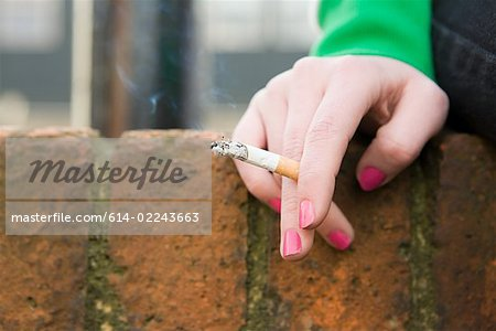 Hand of a girl with cigarette Stock Photo - Premium Royalty-Free, Image code: 614-02243663