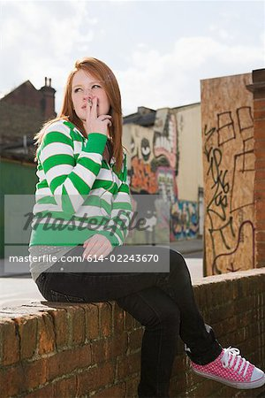 Girl sitting on wall and smoking Stock Photo - Premium Royalty-Free, Image code: 614-02243670
