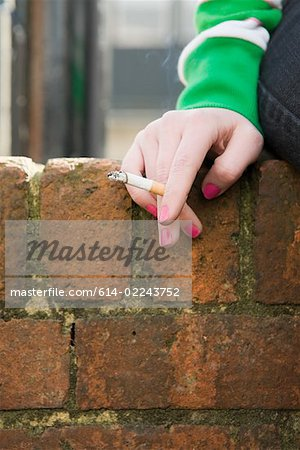 Hand of a girl with cigarette Stock Photo - Premium Royalty-Free, Image code: 614-02243752