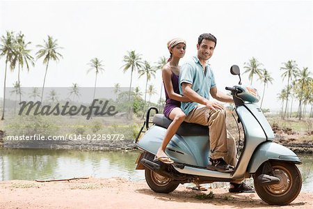 Couple on a moped Stock Photo - Premium Royalty-Free, Image code: 614-02259772