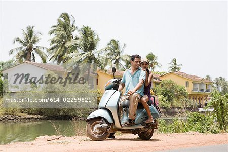 Couple on moped Stock Photo - Premium Royalty-Free, Image code: 614-02259821