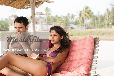 Couple in sunloungers with watermelon slices Stock Photo - Premium Royalty-Free, Image code: 614-02259823