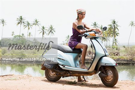 Young woman on moped Stock Photo - Premium Royalty-Free, Image code: 614-02259838