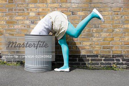 Woman looking in a dustbin Stock Photo - Premium Royalty-Free, Image code: 614-02343952