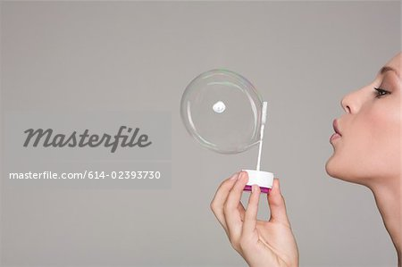 Young woman blowing a bubble Stock Photo - Premium Royalty-Free, Image code: 614-02393730