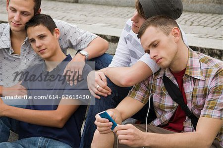 Friends sitting on steps Stock Photo - Premium Royalty-Free, Image code: 614-02613430