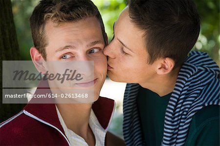 A man kissing his partner on the cheek Stock Photo - Premium Royalty-Free, Image code: 614-02613468