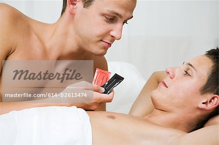 A man handing condoms to his partner Stock Photo - Premium Royalty-Free, Image code: 614-02613474