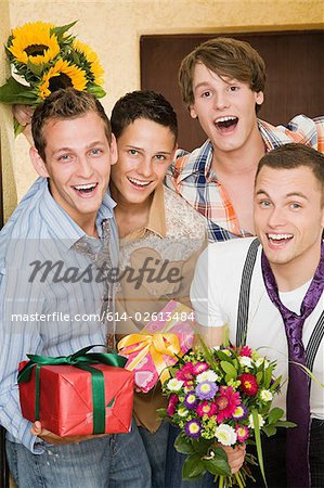 Portrait of friends with flowers and gifts Stock Photo - Premium Royalty-Free, Image code: 614-02613484