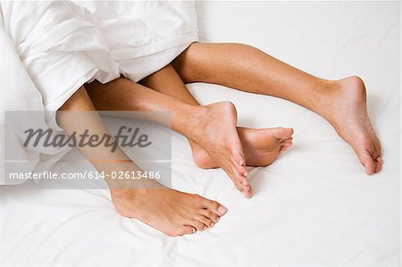 Legs sticking out of a duvet Stock Photo - Premium Royalty-Free, Image code: 614-02613486