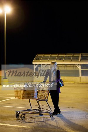 Woman alone in supermarket parking lot Stock Photo - Premium Royalty-Free, Image code: 614-02739729