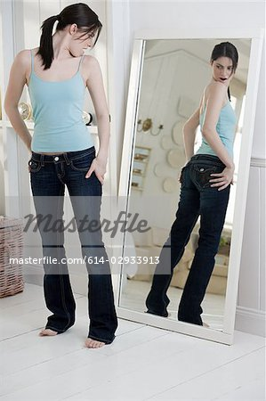 Young woman looking at bottom in mirror Stock Photo - Premium Royalty-Free, Image code: 614-02933913