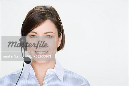 Woman wearing telephone headset Stock Photo - Premium Royalty-Free, Image code: 614-02933971
