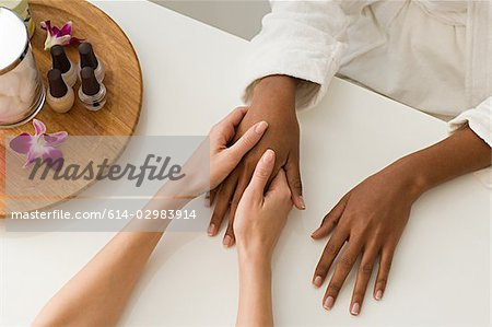 Woman having hands massaged Stock Photo - Premium Royalty-Free, Image code: 614-02983914